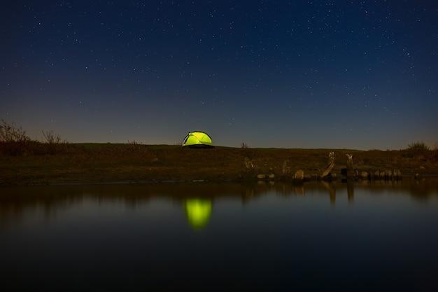 Ночное небо со звездами над туристической палаткой у реки. пейзаж сфотографирован на длинной выдержке.