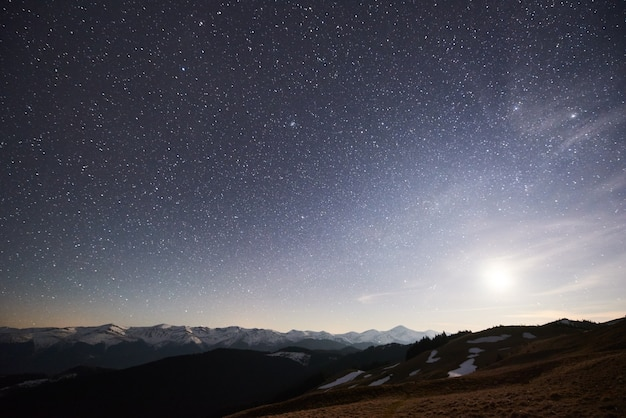 Night sky with stars shining above mountain peak