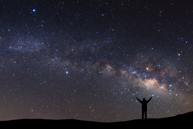 Night sky with stars and silhouette of a standing sporty man with raised up arms