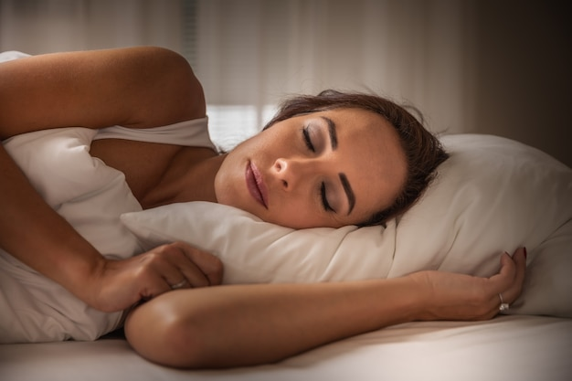 頭の下に白い枕と毛布をかぶった女性の夜の眠り。