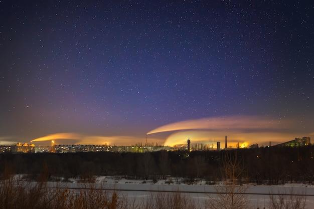도시의 산업 지역에 별이 빛나는 밤하늘. 러시아의 겨울에 촬영 된 풍경