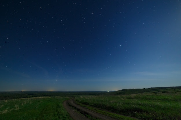 Night starry sky above the road in the countryside