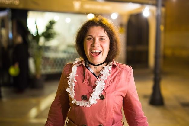파티 후 웃는 아름 다운 젊은 여자의 밤 거리 초상화