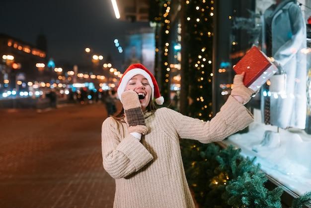 연기하는 젊은 아름 다운 여자의 밤 거리 초상화 감동. 축제 화환 조명.