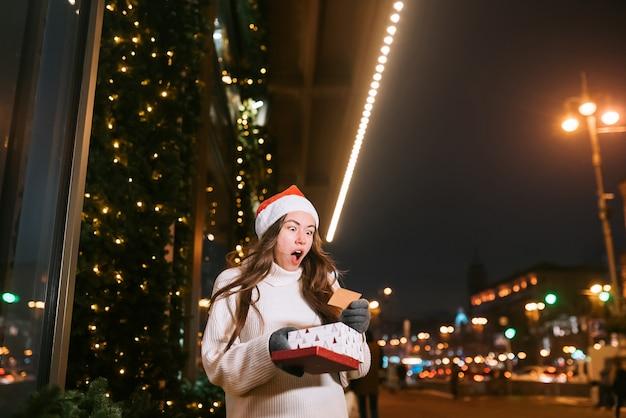 Ritratto di strada di notte di giovane bella donna che agisce entusiasta. luci festive della ghirlanda.