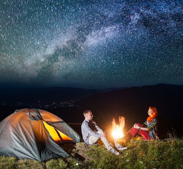 Night tent camping. couple tourists sitting by campfire