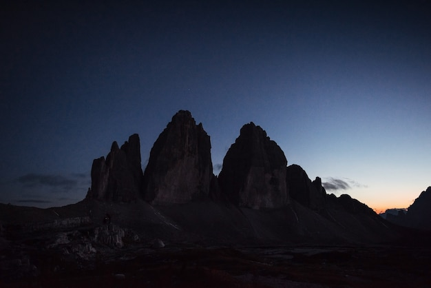 Night time landscape photo. tre cime mountains with three peaks. two hikers working with photo camera far away on the left.