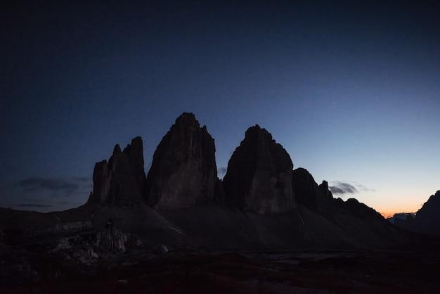 Фото ночного пейзажа. горы тре чиме с тремя вершинами. два туриста работают с фотоаппаратом далеко слева.
