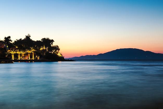 ケファロニア島のザキントス島からの夜の熱帯の風景。日没時の燃えるような空、ヤシの木とホテルのシルエット、ギリシャ