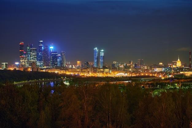 高層ビルのあるモスクワ市のダウンタウンのビジネスセンターとモスクワの夜の都市景観パノラマ。照らされた街の街並み。モスクワ。ロシア。