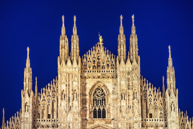 Night view of famous milan cathedral duomo di milano on piazza in milan, italy with stars on the blue dark sky
