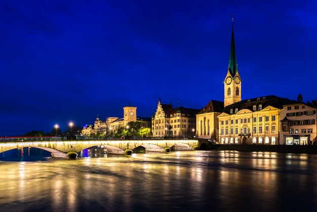 Night view of historic zurich city center with famous church and river limmat in switzerland.