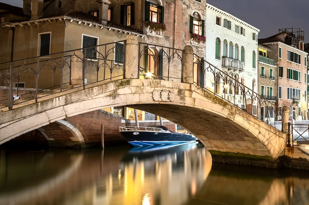 Night view of illuminated old buildings, floating boats and light reflections in canal water in venice, italy.