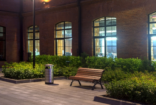 Night view. industrial building. office buildings. empty bench and urn. red brick house.
