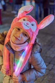 Ночная точка зрения улыбающейся девушки в розовой шляпе с зажженными ушами на рождество в толедо, испания
