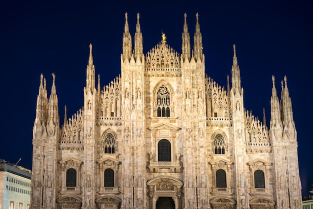 Ночной вид на знаменитый миланский собор (duomo di milano) на площади в милане, италия со звездами на синем темном небе