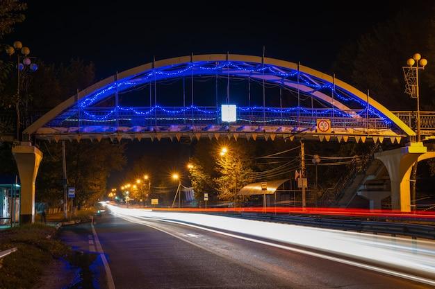 다리의 배경에 동작 흐림 효과가 있는 고속도로의 야경. 밤 고속도로입니다.