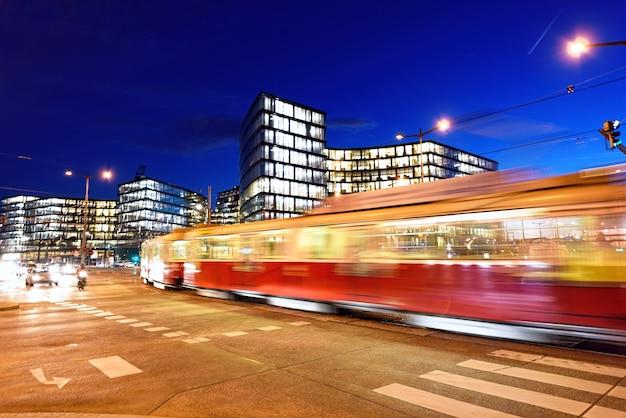 Ночной вид на уличные и стеклянные бизнес-здания в вене, автомобили и трамвай