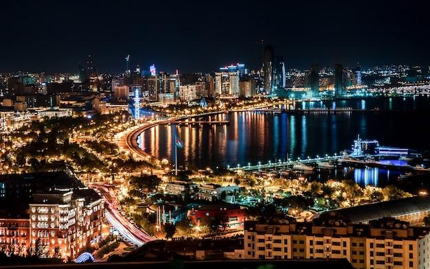 Ночной вид на горизонтальный городской пейзаж на побережье с огнями