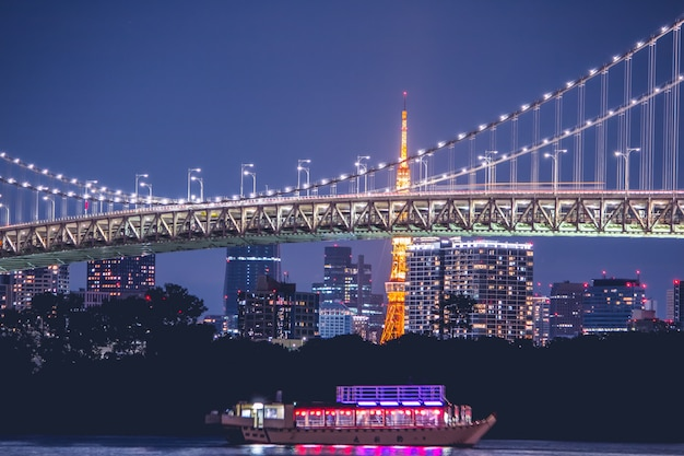 Night view rainbow bridge and tokyo tower. the cruise is sail in tokyo bay, odaiba at night, japan