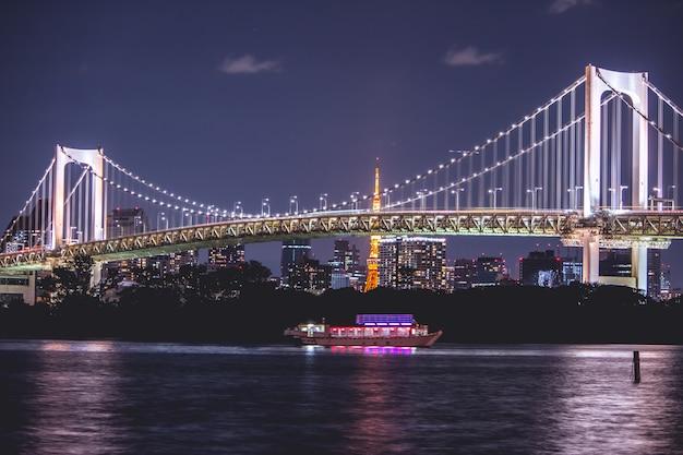 Night view rainbow bridge and tokyo tower. the cruise is sail in tokyo bay, odaiba at night, japan