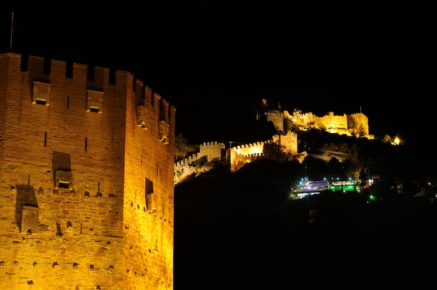 Night view of red tower (kizil kule) and ancient stone wall of alanya castle, turkey