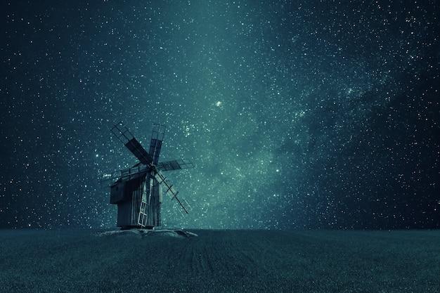 필드에 오래 된 풍차, 하늘에 밝은 별, 끝없는 은하와 밤 빈티지 풍경. 필름 필터