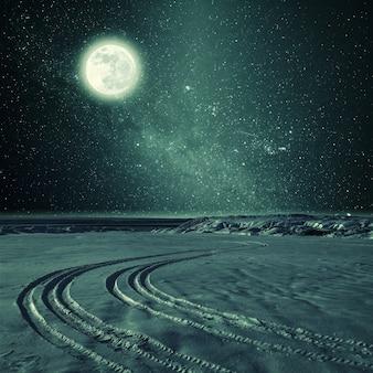 Ночной старинный пейзаж со следом шин на снегу, звездах и полной луне в небе. пленочный фильтр