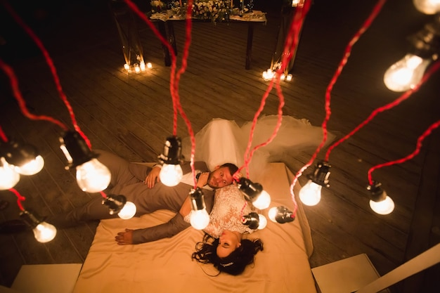 The night wedding ceremony. the bride and groom are lying on the bed