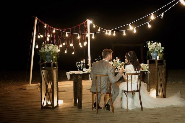 The night wedding ceremony. the bride and groom are sitting at the festive table. banquet
