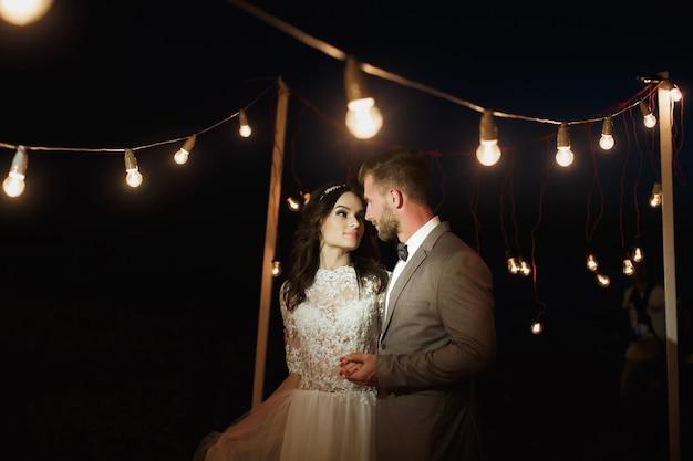 Night wedding ceremony. the bride and groom hugging.