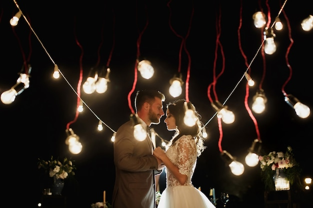 The night wedding ceremony. bride and groom looking at each other in the background