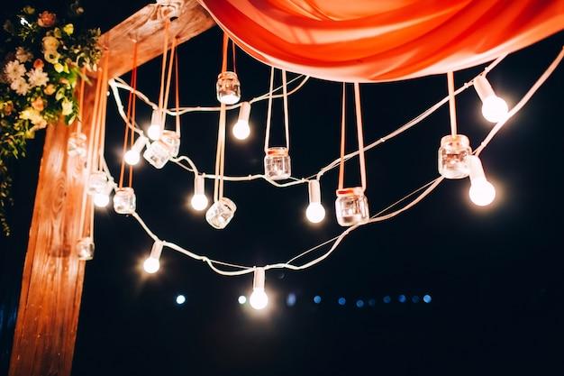 Ночная свадебная церемония. свадьба вечером украшена аркой. гирлянда из лампочек. свечи в стеклянных колбах.