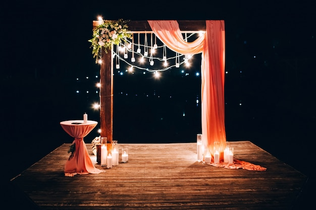 Night wedding ceremony. wedding is decorated with an arch in the evening. garland of light bulbs. candles in glass flasks.