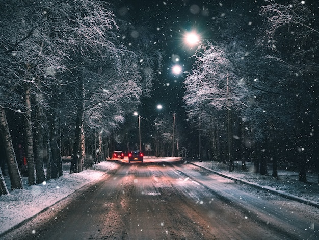 Night winter rural road with driving car.
