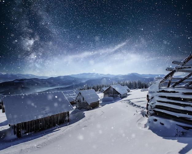 Ночь со звездами. рождественский пейзаж. деревянный дом в горной деревне. ночной пейзаж зимой