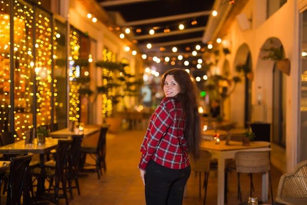 ナイトライフ、人々、そして楽しいコンセプト-美しい若い女性が夜の路上で明るいレストランの近くでポーズをとる。