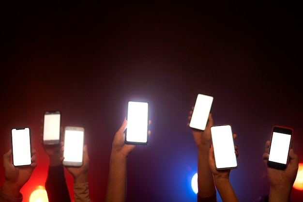 Nightlife of people dancing in a club and holding smartphones up