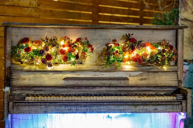 花の装飾品で飾られたledライトと装飾的なレトロな白いピアノのナイトショット