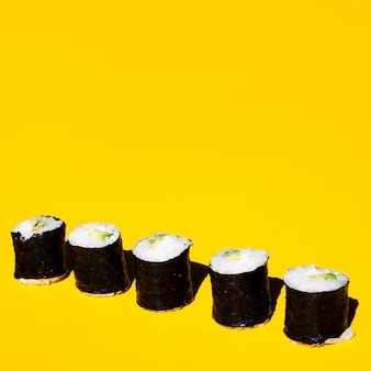 Nigiri rolls on a yellow background