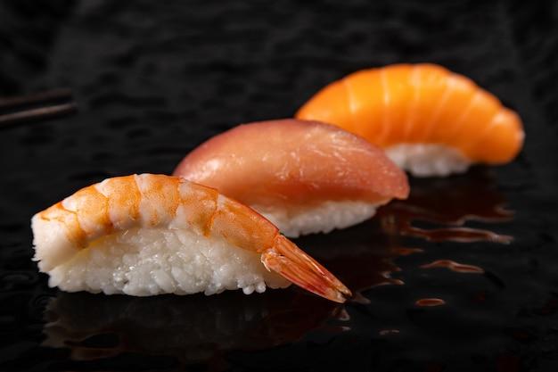 Суши нигири с креветками, лососем и тунцом на черной глянцевой тарелке, выбранный фокус