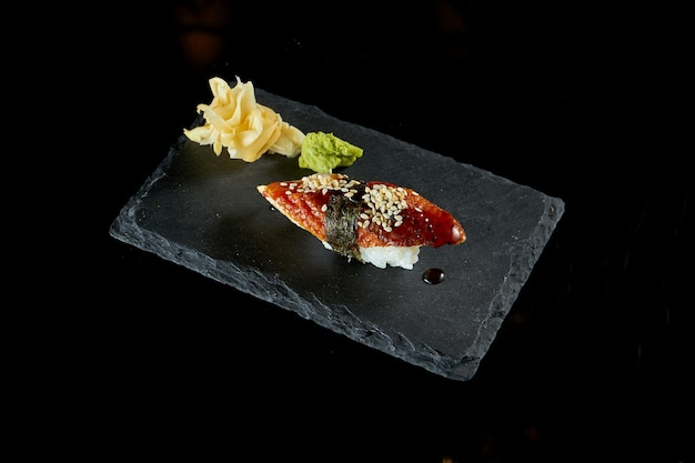 Nigiri sushi with eel and unagi sauce on a black board with ginger and wasabi. japanese kitchen. food delivery. isolated on black