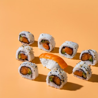 Nigiri sushi with maki rolls on yellow background