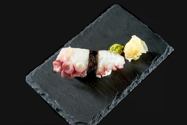 Nigiri sushi with octopus on a black board with ginger and wasabi. japanese kitchen. food delivery. isolated on black