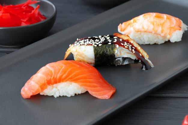 Суши нигири с лососем, угрем и креветками на черной керамической тарелке крупным планом