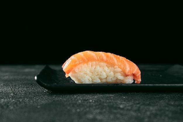 黒い板に鮭をのせたにぎり寿司。日本のキッチン。食品デリバリー。黒の背景