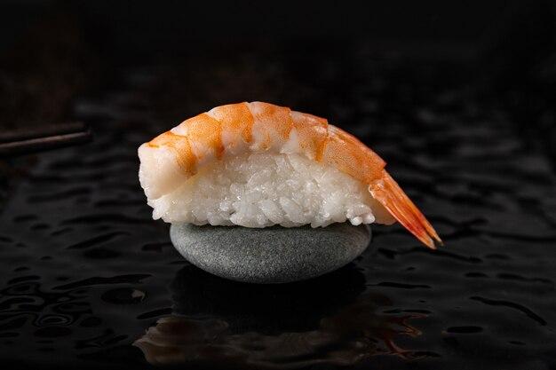 Нигири суши с креветками на камне и черной глянцевой тарелке
