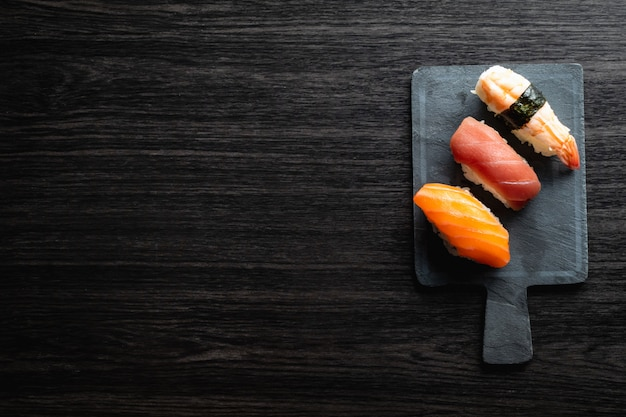 Nigiri sushi on wood table in a japanese restaurant. copyspace and top view
