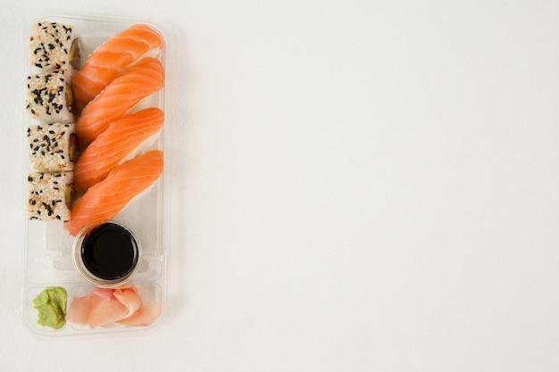 Nigiri and uramaki served with soy sauce in plastic box