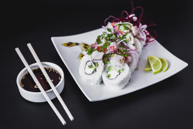 Nikkei ceviche roll on a dark table